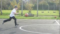 Student dribbling a ball while running